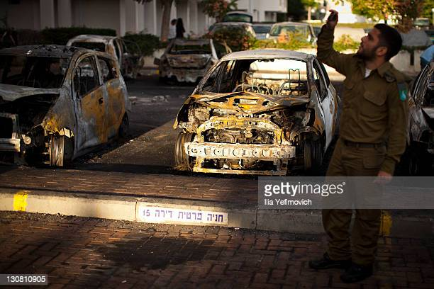 A soldier takes pictures of burnt out cars remaining after a longrange Grad rocket yesterday hit the area on October 30 2011 in Ashdod Israel Moshe...