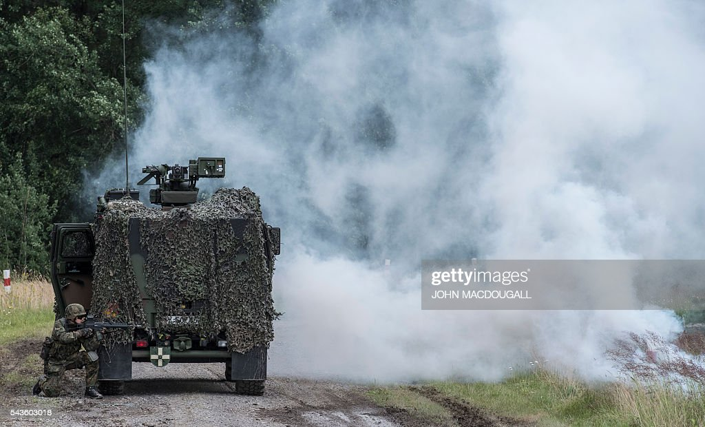 A soldier takes up position next to a light armoured vehicle after an ambush was simulated during a drill at the headquarters of the 33rd Panzergrenadier bataillon in Neustadt am Ruebenberge on June 29, 2016. / AFP / JOHN
