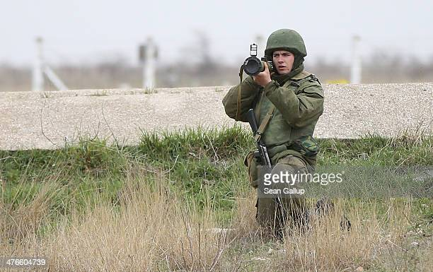 A soldier under Russian command aims a rocket propelled grenade launcher at a group of over 100 hundred unarmed Ukrainian troops who appeared at the...