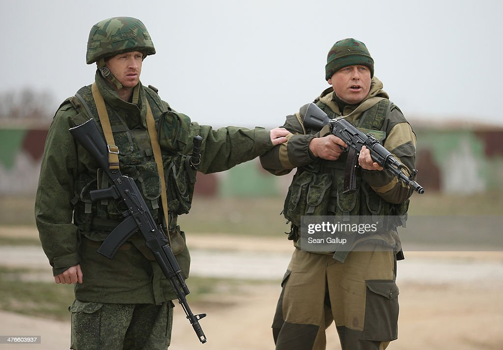 A soldier under Russian command restrains a colleague after he fired his weapon into the air and screamed orders to turn back at an approaching group of over 100 unarmed Ukrainian troops at the Belbek airbase, which the Russian troops are occcupying, in Crimea on March 4, 2014 in Lubimovka, Ukraine. The Ukrainians are stationed at their garrison nearby, and after spending a tense night anticipating a Russian attack following the expiration of a Russian deadline to surrender, in which family members of troops spent the night at the garrison gate in support of the soldiers, their commander Colonel Yuli Mamchor announced his bold plan this morning to retake the airfield by confronting the Russian-lead soldiers unarmed. The Russian-lead troops fired their weapons into the air but then granted Mamchor the beginning of negotiations with their commander. Russian-lead troops have blockaded a number of Ukrainian military bases across Crimea.