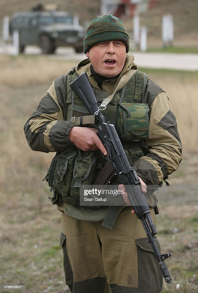 A soldier under Russian command warns anyone approaching further that he will shoot them in the legs after he and colleagues fired their weapons into the air and screamed orders to turn back at an approaching group of over 100 hundred unarmed Ukrainian troops at the Belbek airbase, which the Russian troops are occcupying, in Crimea on March 4, 2014 in Lubimovka, Ukraine. The Ukrainians are stationed at their garrison nearby, and after spending a tense night anticipating a Russian attack following the expiration of a Russian deadline to surrender, in which family members of troops spent the night at the garrison gate in support of the soldiers, their commander Colonel Yuli Mamchor announced his bold plan this morning to retake the airfield by confronting the Russian-lead soldiers unarmed. The Russian-lead troops fired their weapons into the air but then granted Mamchor the beginning of negotiations with their commander. Russian-lead troops have blockaded a number of Ukrainian military bases across Crimea.