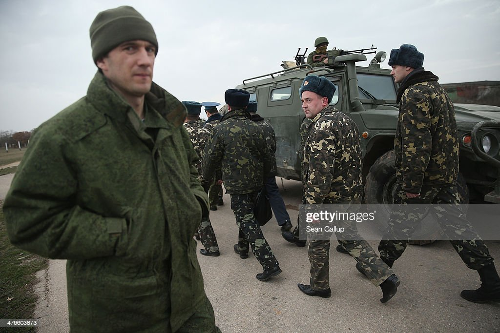 A soldier (L) under Russian command watches as a group of ten Ukrainian troops pass to take positions in the airfield control after over 100 hundred unarmed Ukrainian troops marched up the Belbek airbase, which the Russian troops are occcupying, in Crimea on March 4, 2014 in Lubimovka, Ukraine. The Ukrainians are stationed at their garrison nearby, and after spending a tense night anticipating a Russian attack following the expiration of a Russian deadline to surrender, in which family members of troops spent the night at the garrison gate in support of the soldiers, their commander Colonel Yuli Mamchor announced his bold plan this morning to retake the airfield by confronting the Russian-lead soldiers unarmed. The Russian-lead troops fired their weapons into the air but then granted Mamchor the beginning of negotiations with their commander. Russian-lead troops have blockaded a number of Ukrainian military bases across Crimea.