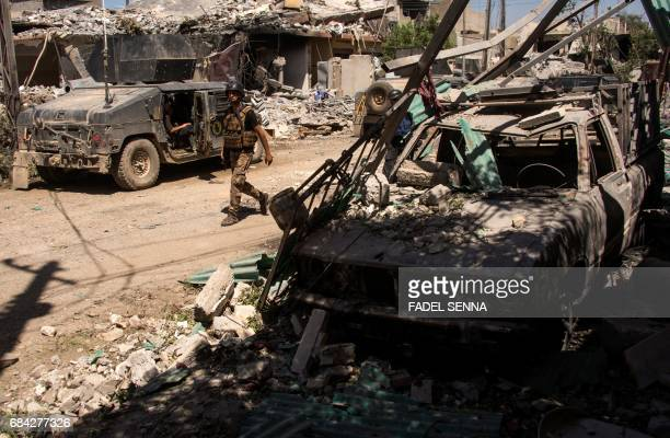 A soldier walks down a street past debris as members of the Iraqi forces take position in a neighbourhood of west Mosul on May 17 during an ongoing...