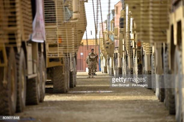 A soldier walks in between two lines of armoured Enhanced Palletised Loading System Vehicle that are preparing to carry out a Combat Logistics Patrol...