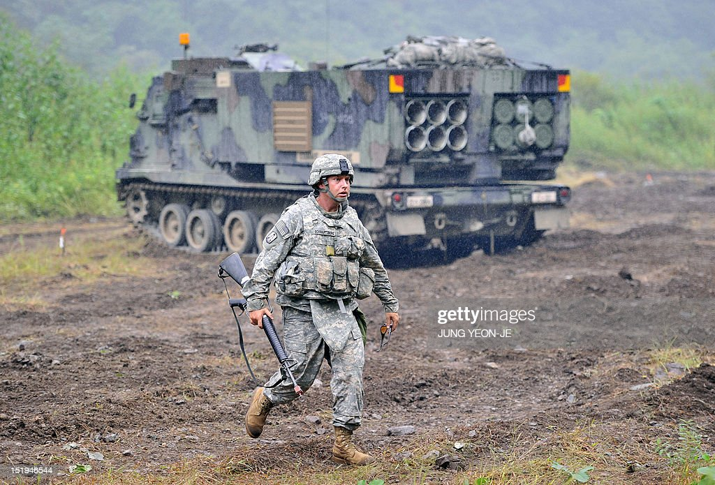 A US soldier walks in front of Multiple Launch Rocket System (MLRS) during a live fire training exercise in the South Korean border county of Cheorwon on September 13, 2012. Some 28,500 US troops are based in South Korea under a mutual defence pact to deter against the North Korean threat. The two Koreas have been technically at war since the conflict ended in an armistice, without a subsequent peace treaty being signed.