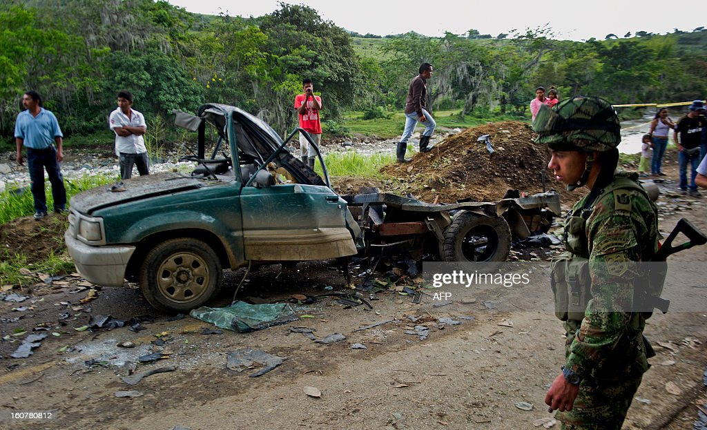 A soldier walks next to the remains of a car bomb in El Palo, department of Cauca, Colombia, on February 5, 2013. Two car bombs were detonated allegedly by Revolutionary Armed Forces of Colombia (FARC) guerrillas at a military checkpoint in southwestern Colombia Tuesday, killing a civilian and a soldier, and injuring three soldiers. AFP PHOTO/LUIS ROBAYO