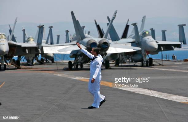A soldier walks next to war jets on the dock of the US aircraft carrier USS George H W Bush as it docks at the Haifa port on July 3 2017 / AFP PHOTO...
