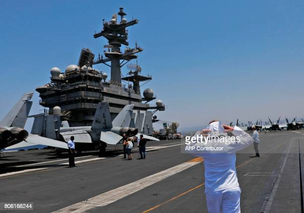 A soldier walks on the dock of the US aircraft carrier USS George H W Bush as it docks at the Haifa port on July 3 2017 / AFP PHOTO / AFP PHOTO AND...