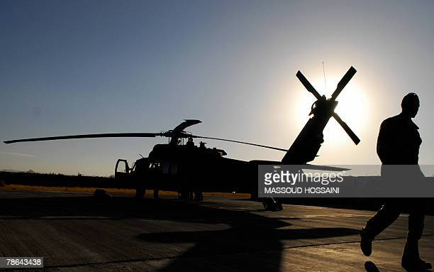 A US soldier walks past an Apache helicopter at Salerno Air field in Khost province 150 kms south east of Kabul 24 December 2007 Around 3000 US...