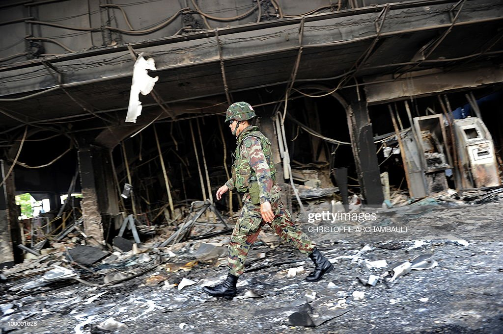 A soldier walks past burnt shops after gunshots were heard near a Buddhist temple in the heart of an anti-government protest zone, in downtown Bangkok on May 20, 2010. Gunshots rang out near a Buddhist temple in the heart of an anti-government protest zone in Bangkok, and soldiers were advancing on foot along an elevated train track, an AFP photographer saw. Thai security forces stormed the 'Red Shirts' protest camp on May 19 in a bloody assault that forced the surrender of the movement's leaders who asked their supporters to disperse. AFP PHOTO/Christophe ARCHAMBAULT