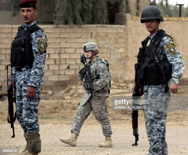 A US soldier walks past Iraqi police commandos during a raid in Baghdad's alBakria district to search for wanted people on March 29 2009 Two Iraqi...