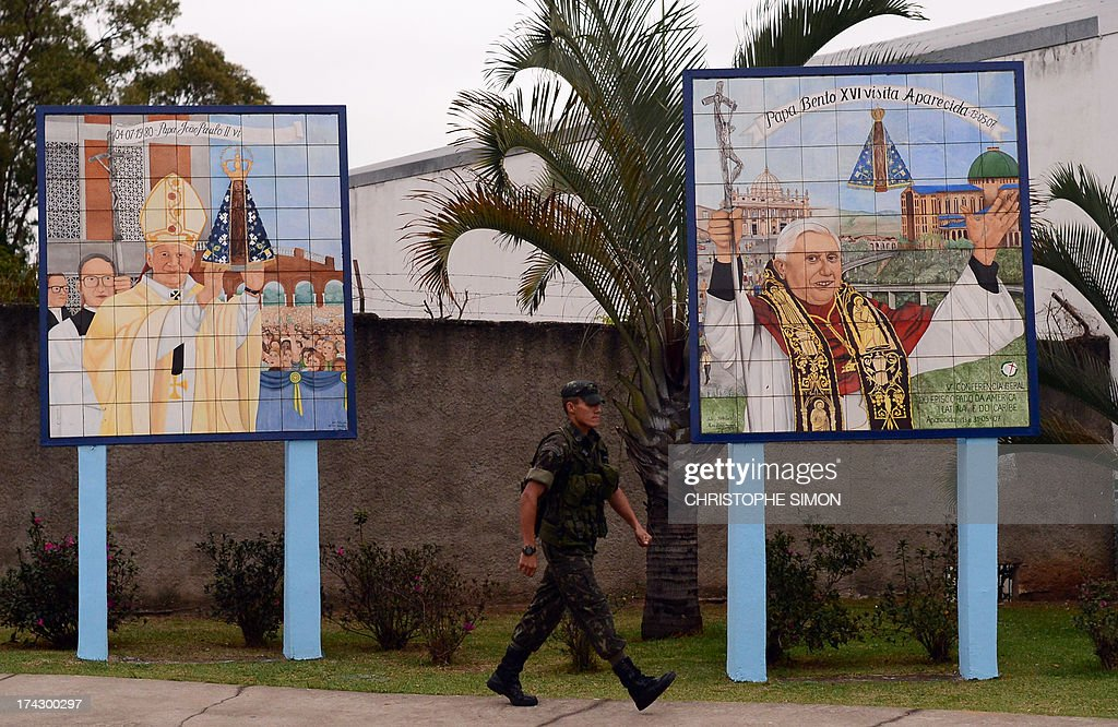 A soldier walks past two mosaics commemorating the visits by late pope John Paul II (L) and retired pope Benedict XVI to the Basilica of the Shrine of Our Lady of the Conception of Aparecida, in Aparecida, in the Brazilian state of Sao Paulo, on July 23, 2013 on the eve a visit by Pope Francis. The highlight of the landmark visit of Pope Francis to the world's most populous mainly Catholic country will be World Youth Day (WYD), a five-day event that kicks off today. Pope Francis's popularity on his Latin American home turf posed a challenge to Brazilian authorities Tuesday after adoring crowds mobbed his car on his arrival on Monday.