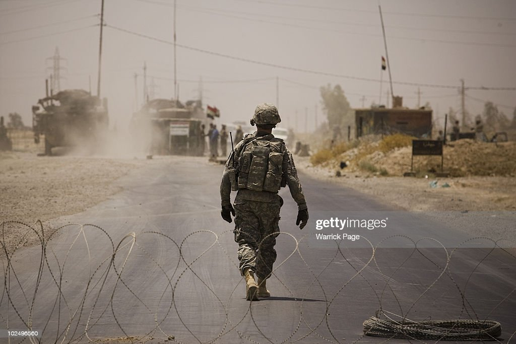 US soldier walks through a flash checkpoint set up in response to the killing of 2 US soldiers in a car bomb attack on June 11 2010 in Ali Ayun...