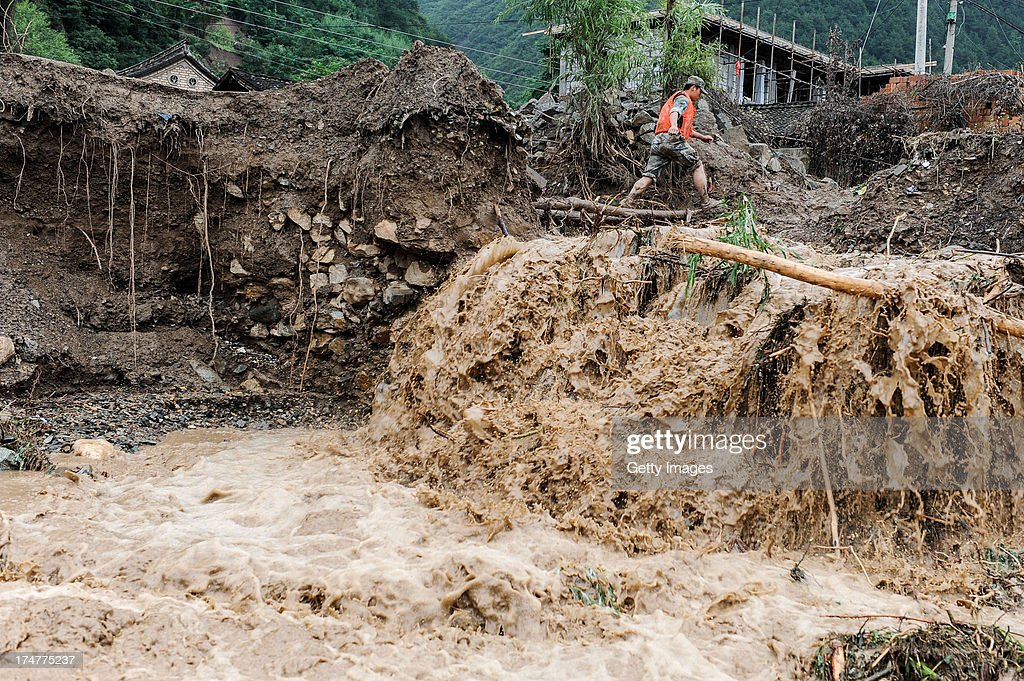 A soldier walks through a flood-hit area on July 28, 2013 in Tianshui, China. At least 22 people were killed and three others missing after rainstorm-triggered floods and landslides hit many places of Tianshui city recently.