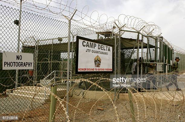 Soldier walks through a gate at Camp Delta at Guantanamo Naval Base August 23 2004 in Guantanamo Cuba On August 24 preliminary hearings will begin...