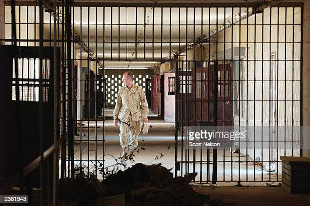 S soldier walks through a hallway of the former Abu Ghraib prison prison August 4 2003 in Baghdad Iraq Which is being cleaned and renovated by the...
