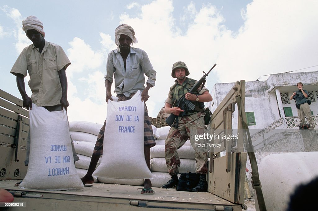 A soldier watches as local men move sacks of beans sent as French aid packages during 'Operation Restore Hope' In the 1980s a civil war erupted in...