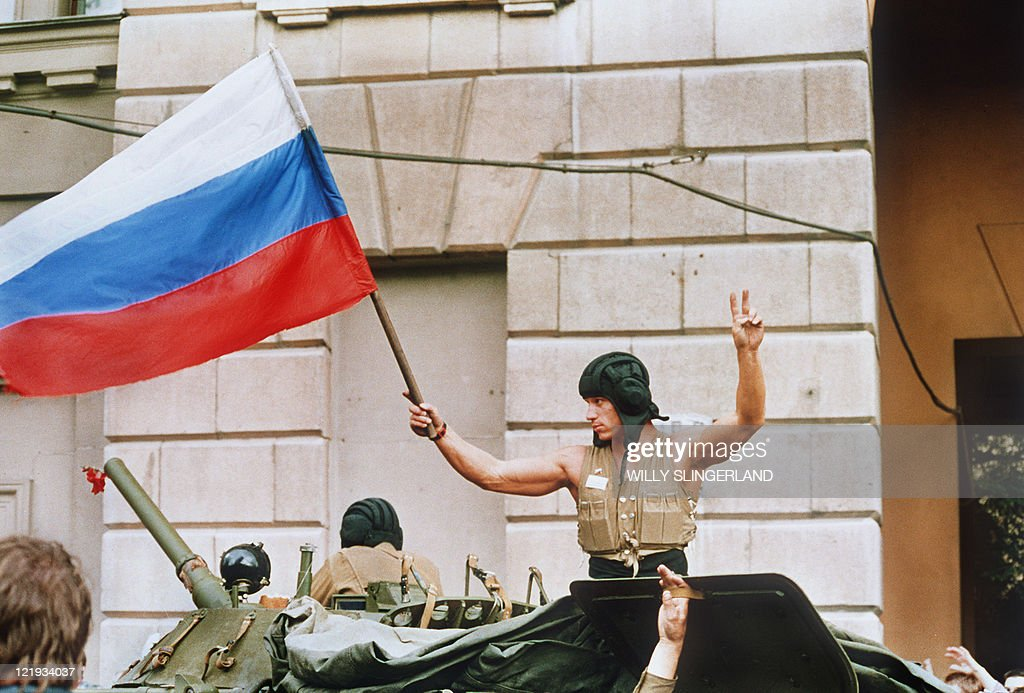 A soldier waves 21 August 1991 a Russian flag from the top of his tank as armoured units leave their positions in Moscow following the collapse of...