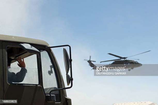 A US soldier waves from a truck as a UH60 Black Hawk helicopter of the 10th Combat Aviation Brigade makes its final approach for landing at Forward...