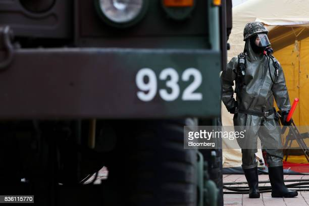 A soldier wearing a gas mask and protective clothing stands next to a military vehicle during a simulated chemical terrorism crisis as part of an...
