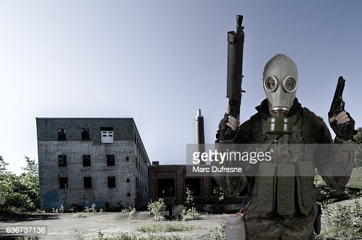 Soldier wearing gas mask holding guns in front of factory