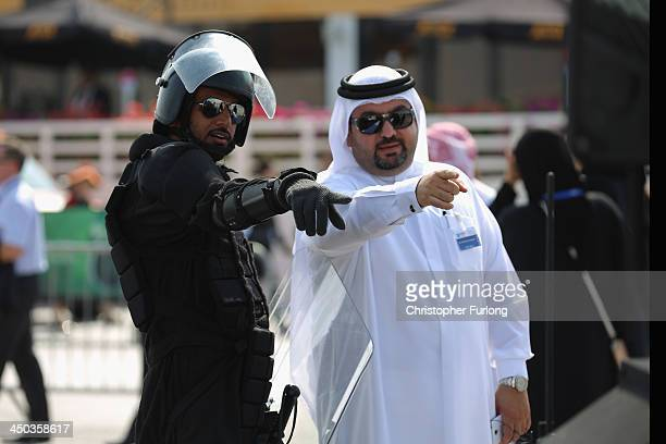 A soldier wearing riot equipment made in the UAE talks to a businessman as they view aircraft during the Dubai Airshow on November 18 2013 in Dubai...