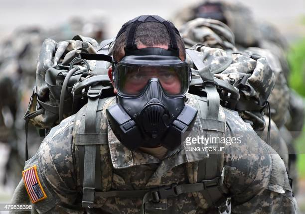 A US soldier wears a gas mask during a competition to test individual skills at a US Army base in Uijeongbu north of Seoul on July 8 2015 The goal of...