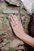 Spouse touches soldier's chest. Soldier's uniform represents deployment due to the multicam pattern.