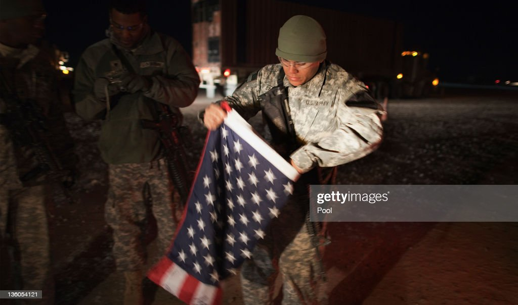 A soldier with the 3rd Brigade Combat Team, 1st Cavalry Division folds up a U.S. flag outside their Mine Resistant Ambush Protected (MRAP) vehicle before leaving Camp Adder to travel with the last U.S. military convoy to leave Iraq on December 18, 2011 near Nasiriyah, Iraq. All U.S. troops were scheduled to have departed Iraq by December 31st, 2011. At least 4,485 U.S. military personnel died in service in Iraq. According to the Iraq Body Count, more than 100,000 Iraqi civilians have died from war-related violence.