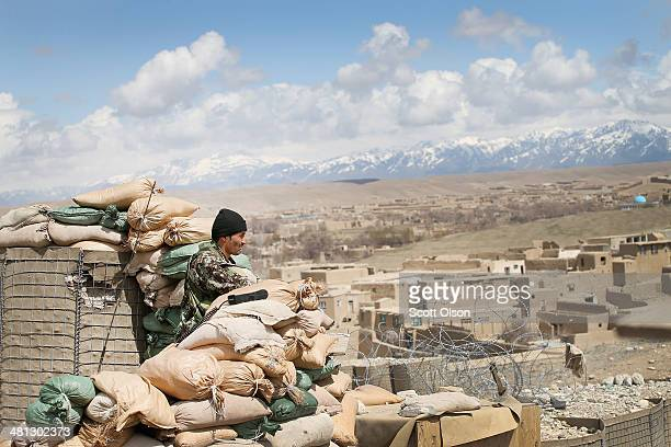 A soldier with the Afghan National Army keeps watch from an outpost near Forward Operating Base Shank on March 29 2014 near Pule Alam Afghanistan...