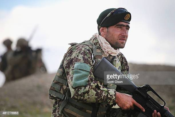 A soldier with the Afghan National Army patrols alongside soldiers with the US Army's 2nd Battalion 87th Infantry Regiment 3rd Brigade Combat Team...