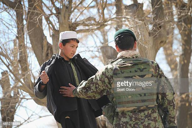 A soldier with the Afghan National Army searches a boy during a patrol with soldiers with the US Army's 2nd Battalion 87th Infantry Regiment 3rd...