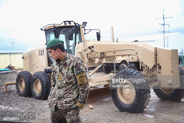 A soldier with the Afghan National Army's 203rd Corps Engineering Kandak stands by one of his unit's CAT graders at Forward Operating Base Thunder on...
