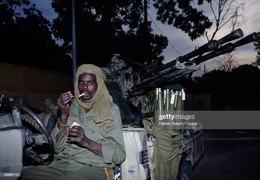 A soldier with the Forces Armees Nationales Chadiennes (FANT), or National Army of Chad, smokes a cigarette while guarding his arsenal of weapons on the streets of N'Djamena. Lead by Chadian Chief of Staff Idriss Deby, the FANT rebellion seized power from head of state Hissen Habre in a French and Libyan-backed military coup. Deby later won the first multi-party Chadian presidential vote in 1996.