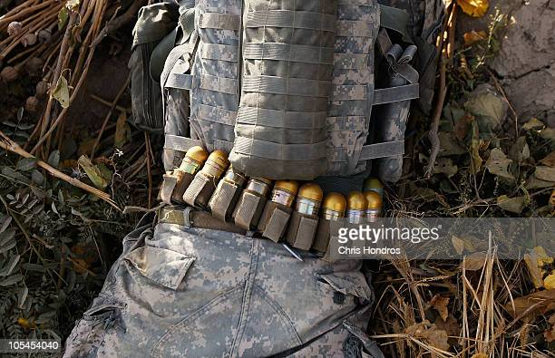 A soldier with the US Army's 101st Airborne Division lies in the dirt with a belt full of launchable grenades during an earlymorning scouting patrol...