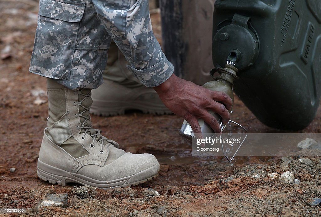 A soldier with the U.S. Army's Second Infantry Division refills his water bottle during an air assault training course at Camp Casey in Dongducheon, South Korea, on Tuesday, Feb. 26, 2013. The U.S. has 28,500 soldiers in South Korea as a legacy of the 1950-53 Korean War, which ended in a cease-fire that left the two Koreas technically still at war. Photographer: SeongJoon Cho/Bloomberg via Getty Images