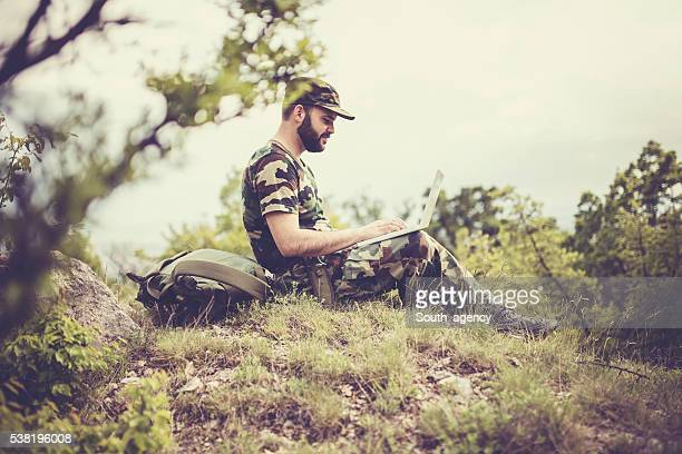 Soldier works on laptop