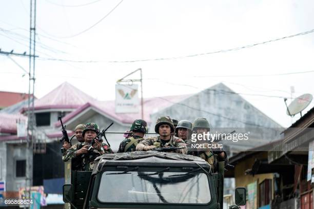 Soldiers aboard a vehicle manoeuvre through a street in Marawi on the southern island of Mindanao on June 14 2017 The Philippine military has for...