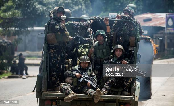 Soldiers aboard their vehicles maneouver through a street in Marawi in southern island of Mindanao on June 10 2017 United States special forces are...