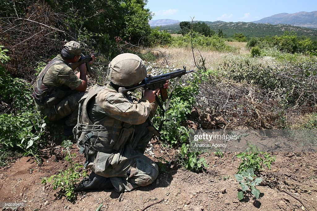 Soldiers aim their rifles as the members of the 'Flag-14 Martyred Gendarme Lieutenant Abdulselam Ozatak Joint Special Forces' destroy cannabis fields during an operation in Diyarbakir, Turkey on June 26, 2016. The 'Flag-14 Martyred Gendarme Lieutenant Abdulselam Ozatak Joint Special Forces Operation' continues, with 24 batallions under the 7th Diyarbakr Corps Command in Lice and surrounding areas. The operation, begun in mountain and forest areas where high ranking terrorist commanders are believed to be sheltering, aims to render terrorists ineffective, destroy areas of cannabis cultivation that serve as sources of finance for the terrorist organization and take apart shelters and depots, and continues with its successes. As part of the operation, 6 million 438 thousand cannabis plants have been uprooted and destroyed. The aim is to dry up one of the biggest sources of finance for the PKK terrorist organization.