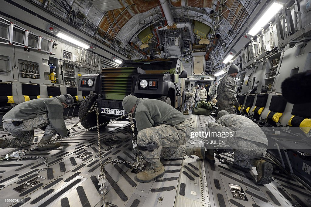 US soldiers American stow a French armored vehicle aboard a C17 aircraft of the US Airforce at the Istres military airport (BA 125) on January 24, 2012, prior to take off and heading toward Mali as part of the 'Serval' operation.