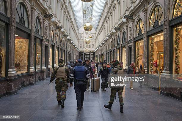 Soldiers and a police officer pass shoppers and tourists as festive decorations hang inside Galeries Royales SaintHubert luxury shopping arcade in...