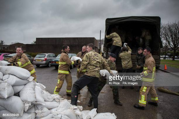 Soldiers and firefighters load up sandbags onto a lorry in Datchet Berkshire to help to defend the town from the floods that have brought misery to...