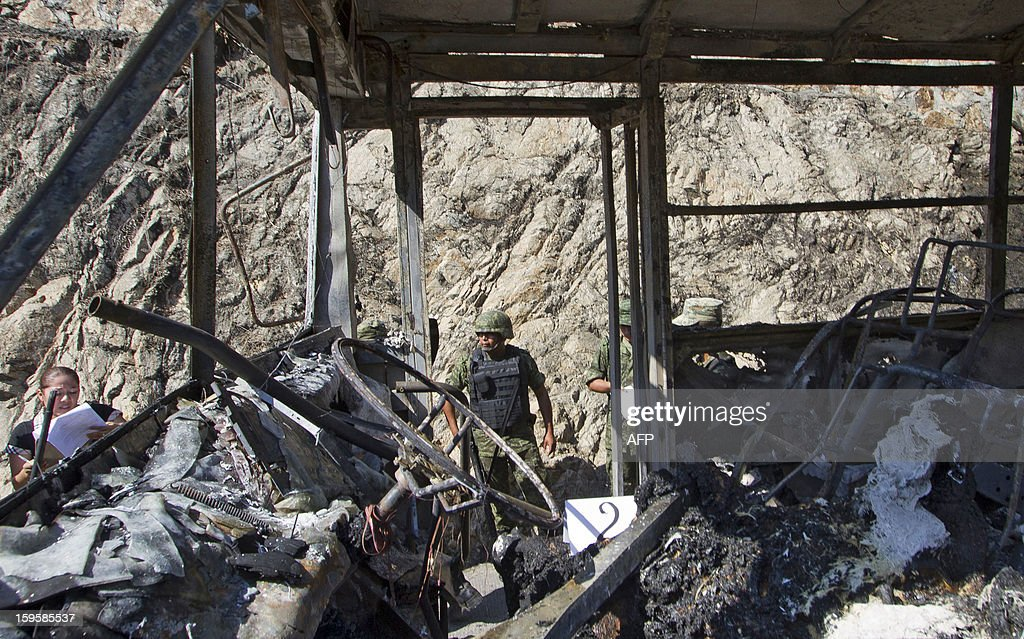 Soldiers and forensic personnel remain next to a bus set ablaze in Mozimba neighborhood, Acapulco, Guerrero State, Mexico on January 16, 2013. The bus was attacked by unkown gunmen who evacuated passengers and killed the driver and his 14-year-old assistant before setting fire to the bus. AFP PHOTO/ Pedro Pardo
