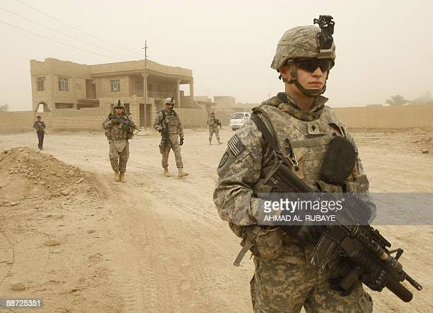 US soldiers and Iraqi police carry out their last patrol along the streets of Khan Bani Saad some 10 kms south of the town of Baquba on June 28 2009...