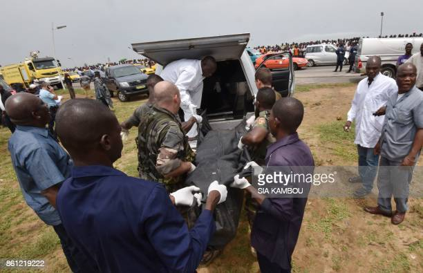 Soldiers and members of funeral services transport a body bag containing the corpse of one of the four people killed in the crash of a cargo plane...