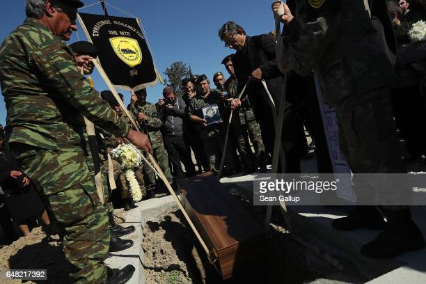 Soldiers and pallbearers lower the small coffin containing the remains of Georgiou Theodoulos Theodoulou at his funeral on March 5 2017 in Pera...