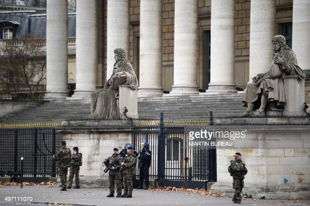 Soldiers and police officers stand guard outside the Assemblee Nationale in Paris on November 14 the day after a total of six separate attacks which...