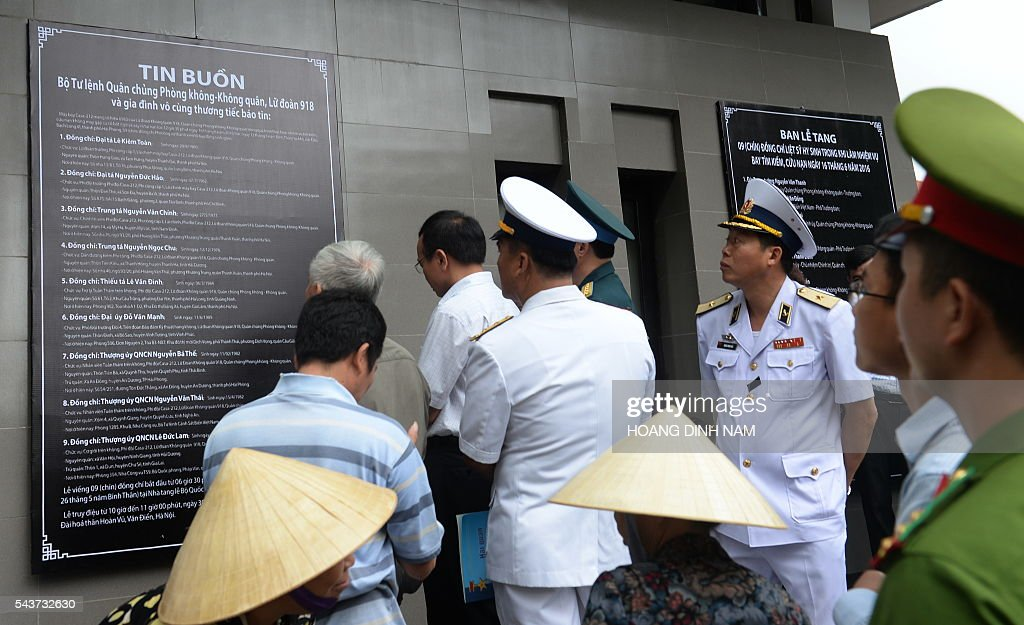 Soldiers and relatives look at the list bearing names (L) of nine victims of a rescue aircraft that crashed on June 16, 2016 over the South China Sea during a search mission for a Vietnamese Airforce Sukhoi SU-30MK2 that went missing two days earlier, during an official funeral ceremony in Hanoi on June 30, 2016. / AFP / HOANG