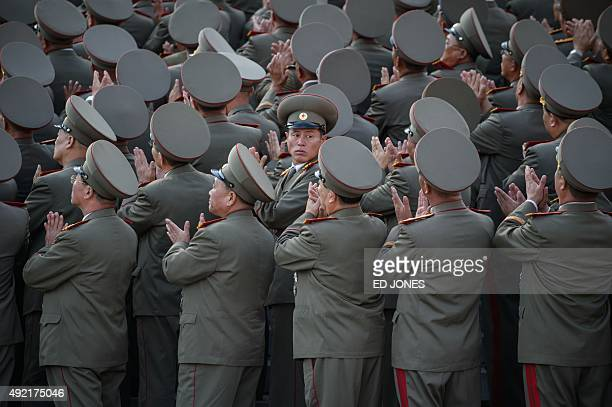 Soldiers applaud the arrival North Korean leader Kim JongUn during a mass military parade at Kim IlSung square in Pyongyang on October 10 2015 North...